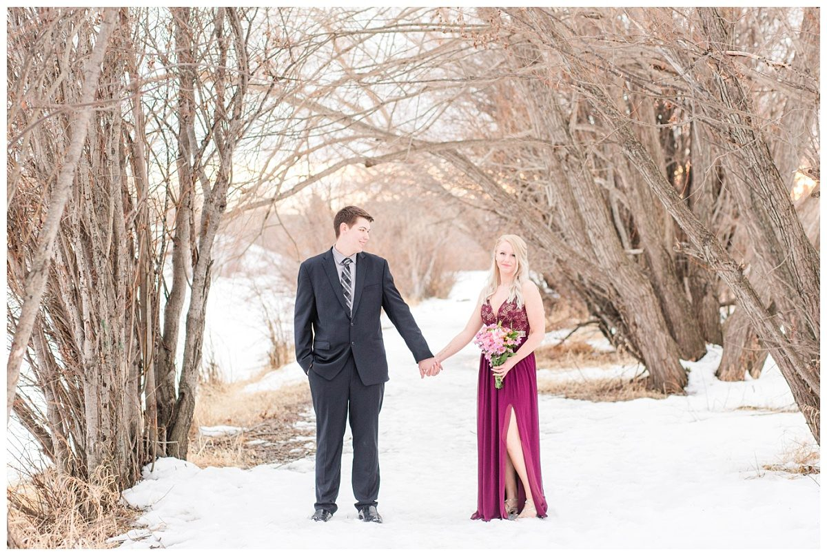 couple at engagement session with grande prairie wedding photographer holding hands along the path of trees full of snow