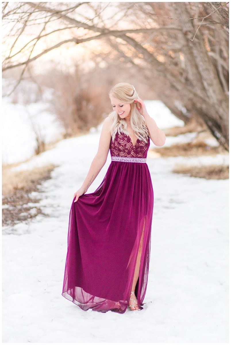the bride with flowy long purple dress kaytlin with blond hair at her engagement session with grande prairie wedding photographer with snow in the background