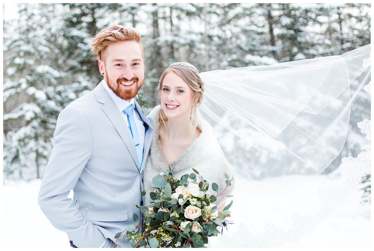 winter wedding couple in grande prairie for styled shoot with light pastel colors and veil from castapella