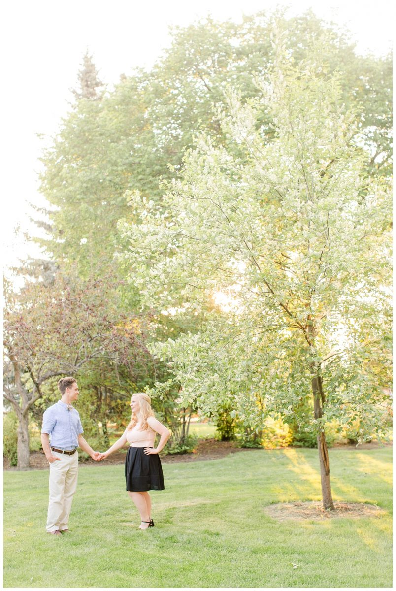 kyle and laurella couple holding hands during their engagement session with the blossom tree and glowing light in the background lots of summer greens blush and black dress with light blue dress shirt