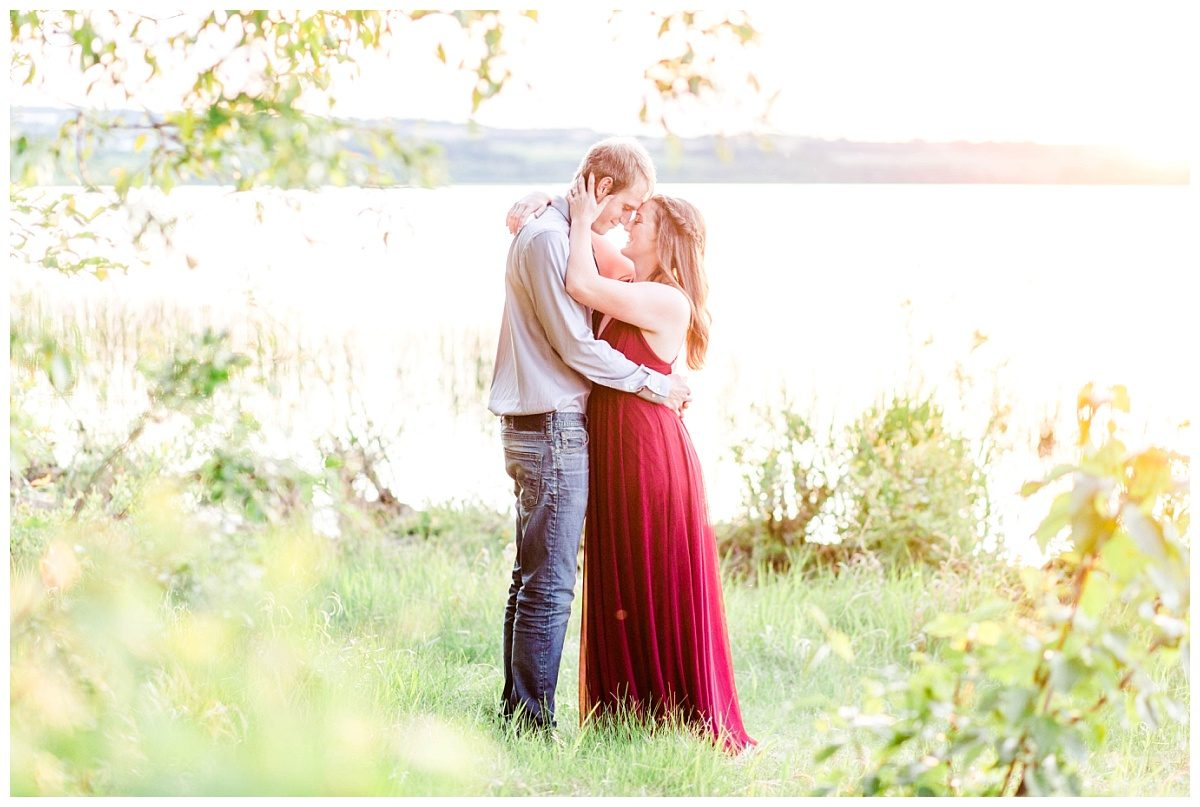 romantic photo in grande prairie cache with shelbee in her red dress full of greenery by the lake with wedding photographer