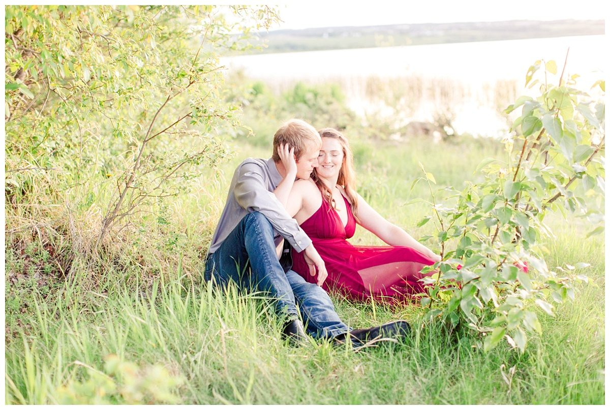 couple sitting down for their engagement photos in the outdoors in the summer with lots of greenery in front of a lake in grande prairie