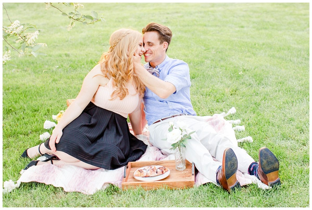 cute picnic theme with engaged couple in grande prairie with photographer and blossoms in the summer time really cute picnic theme set up