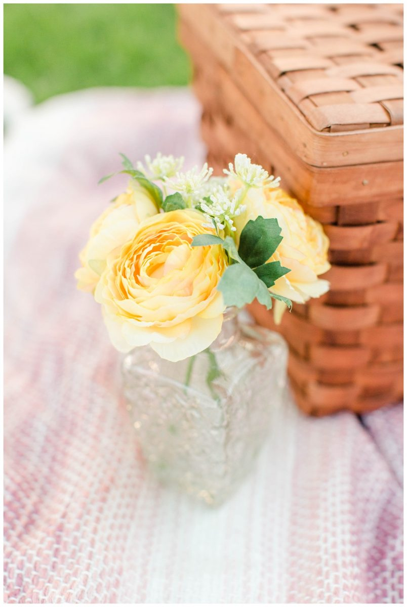picnic theme yellow flowers close up sitting on blush patterned blanket with basket on the right side