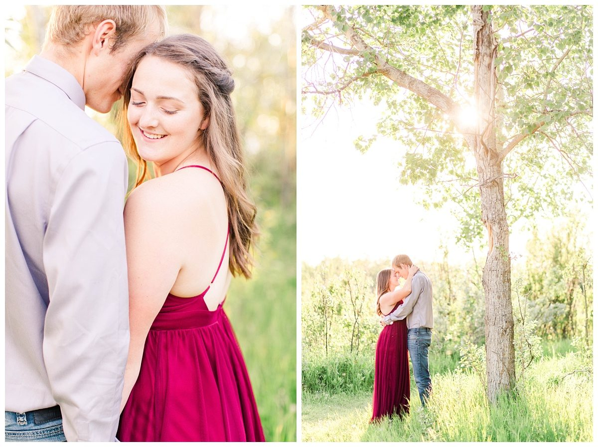 shelbee looking over shoulder couple inder a trees for their grande prairie cache engagement session with dress that is red and sunlight golden hour