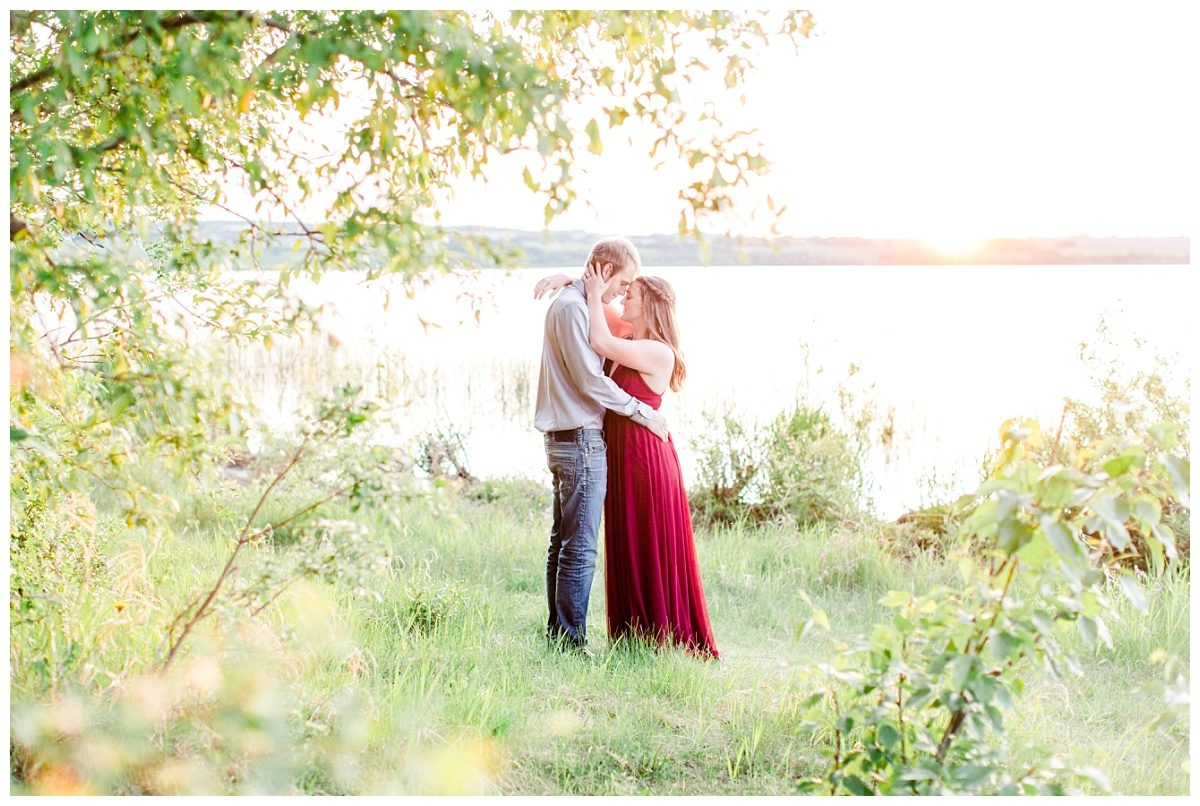 grande cache wedding couple with kayla lynn photographer engagement photos with the red dress in a grande prairie lake location with lots of greens