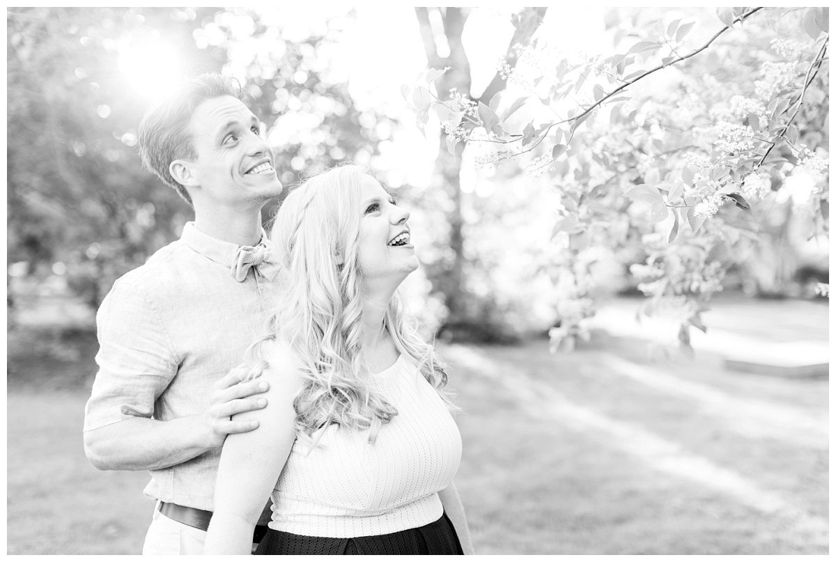 kyle and laurella black and white photo smiling at trees really happy couple in love engaged