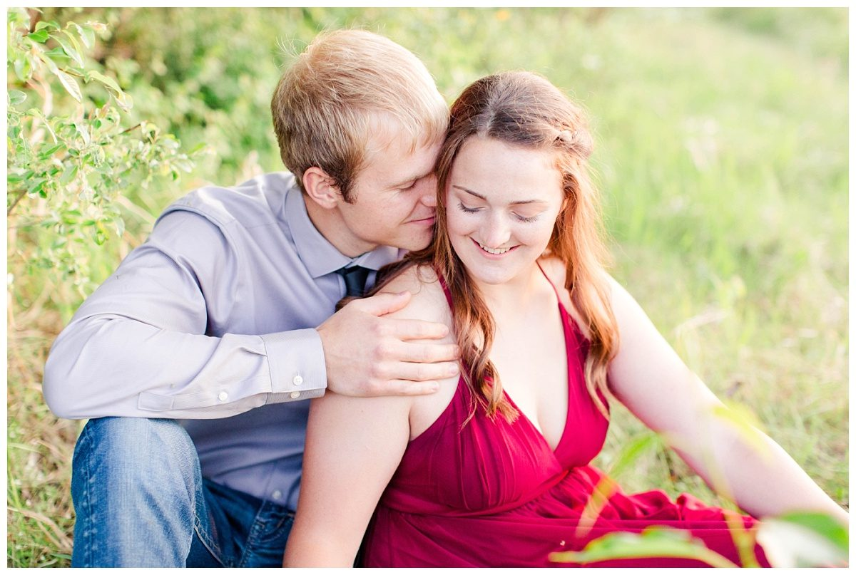 danial and shelbee nuzzle sitting pose happy couple with red dress for outfoor engagement session in grande prairie