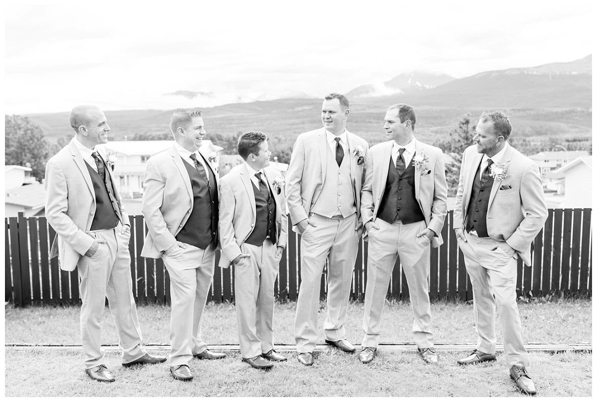 groomsmen photo black and white laughing with mountains in the background in grande cache