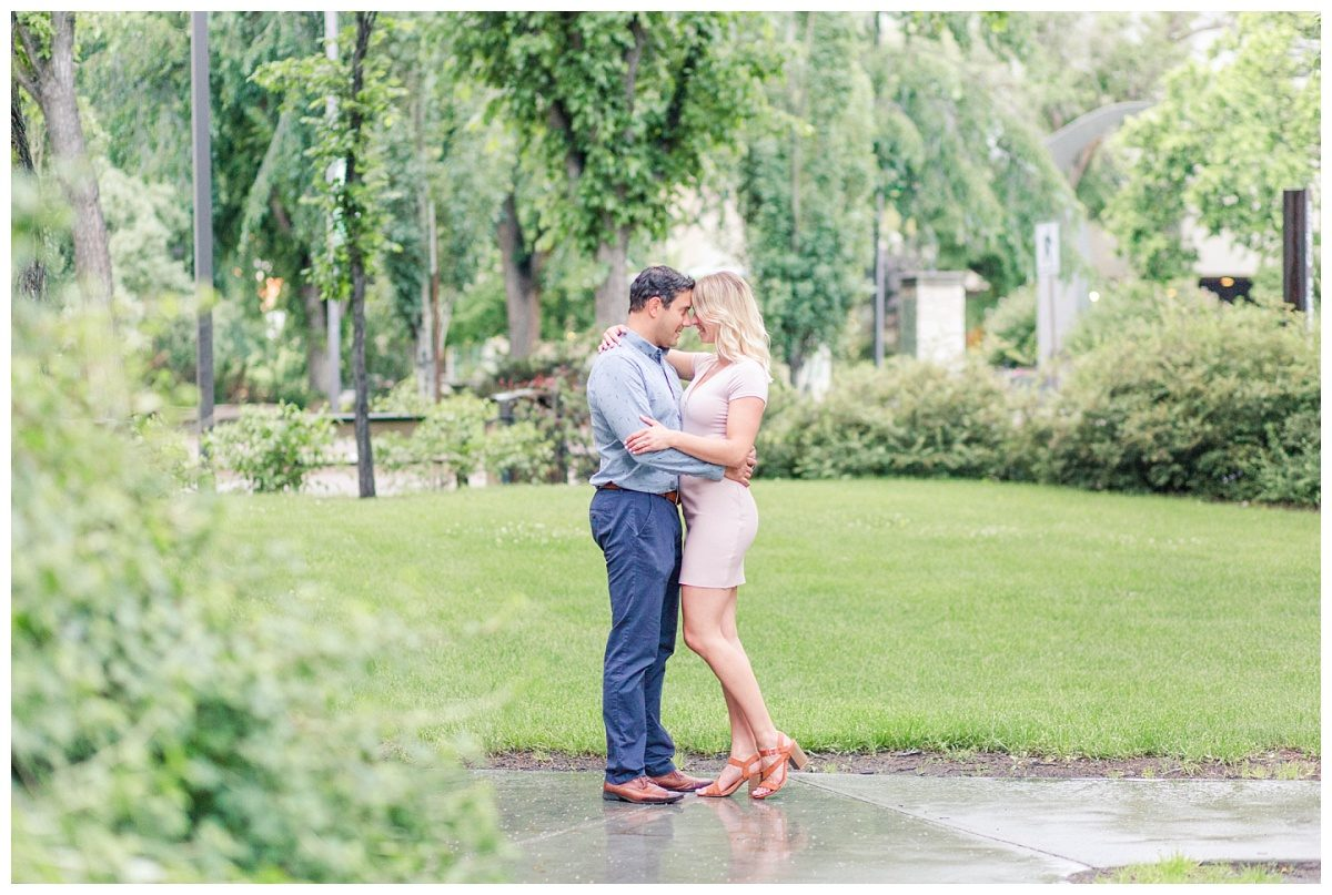 wet ground rainy engagement photos chest to chest with lots of greenery in the background