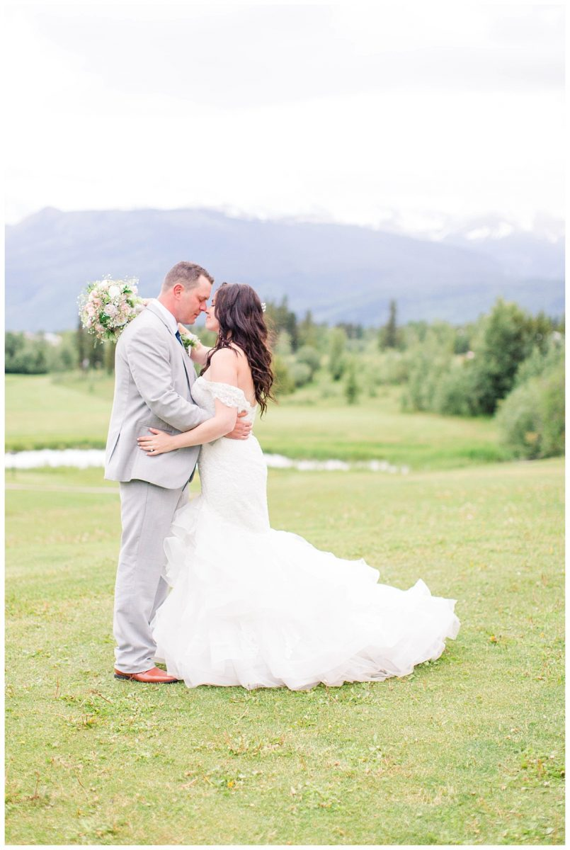 bride and groom portraits at the golf and country club in grande cache with wedding photographer with mountains and trees in the background