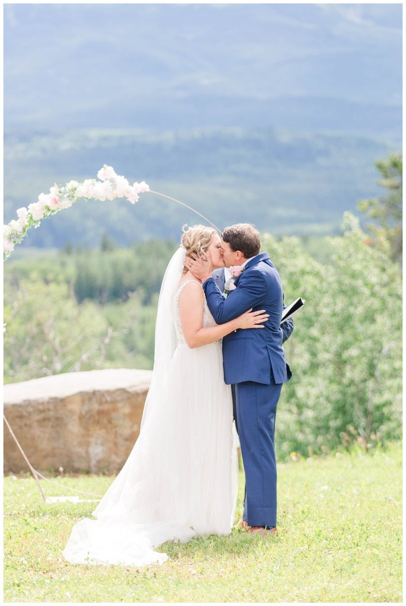 bride and groom share their first kiss at labyrinth in grande cache during their wedding ceremony with floral arch in the background