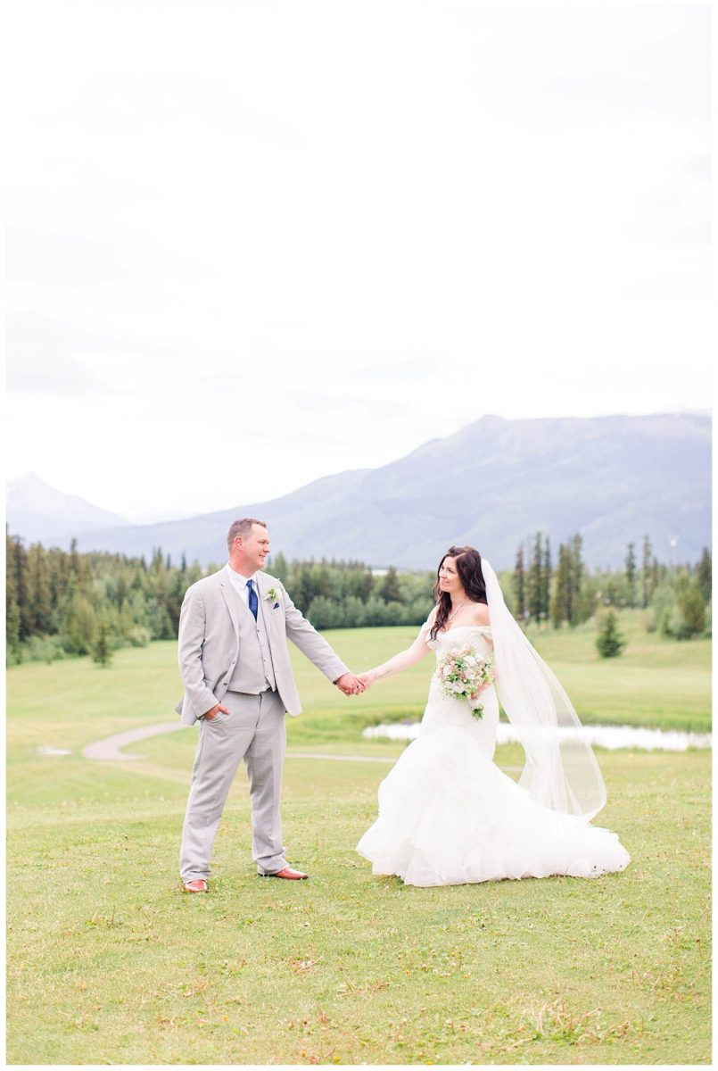 bride and groom portrait holding hands with mountains in grande cache at the wedding venue golf and country club very beautiful wide shot