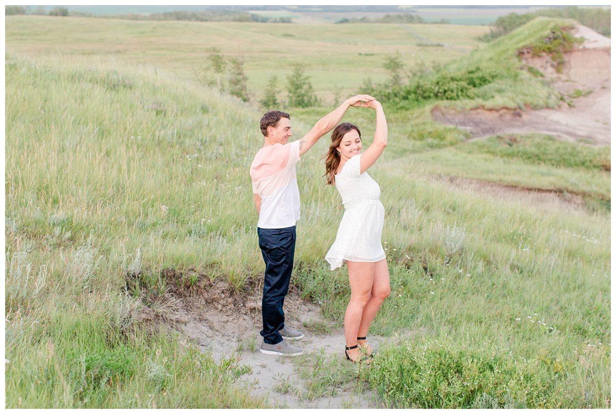 guy twirling girl for engagement session at kleskun hills