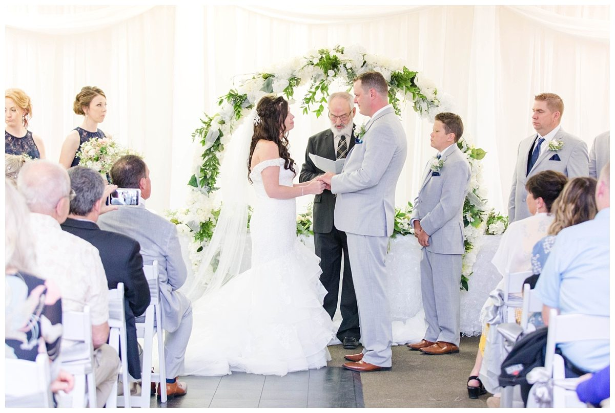 elegant ceremony amanda and corwin white and greenery circular arch grande cache gold and country club indoor ceremony