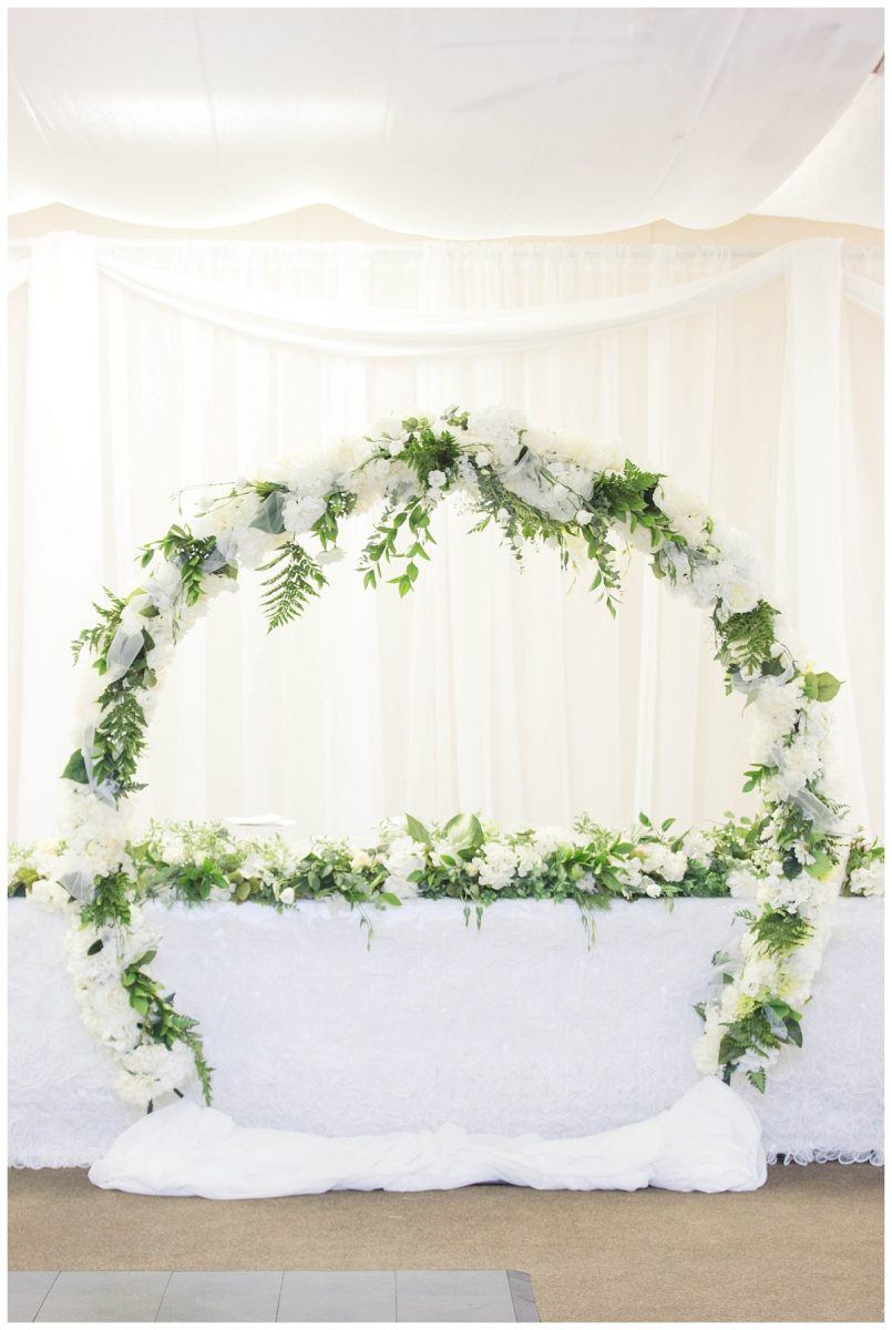 circular greenery arch in the gold and country club grande cache ceremony and reception details