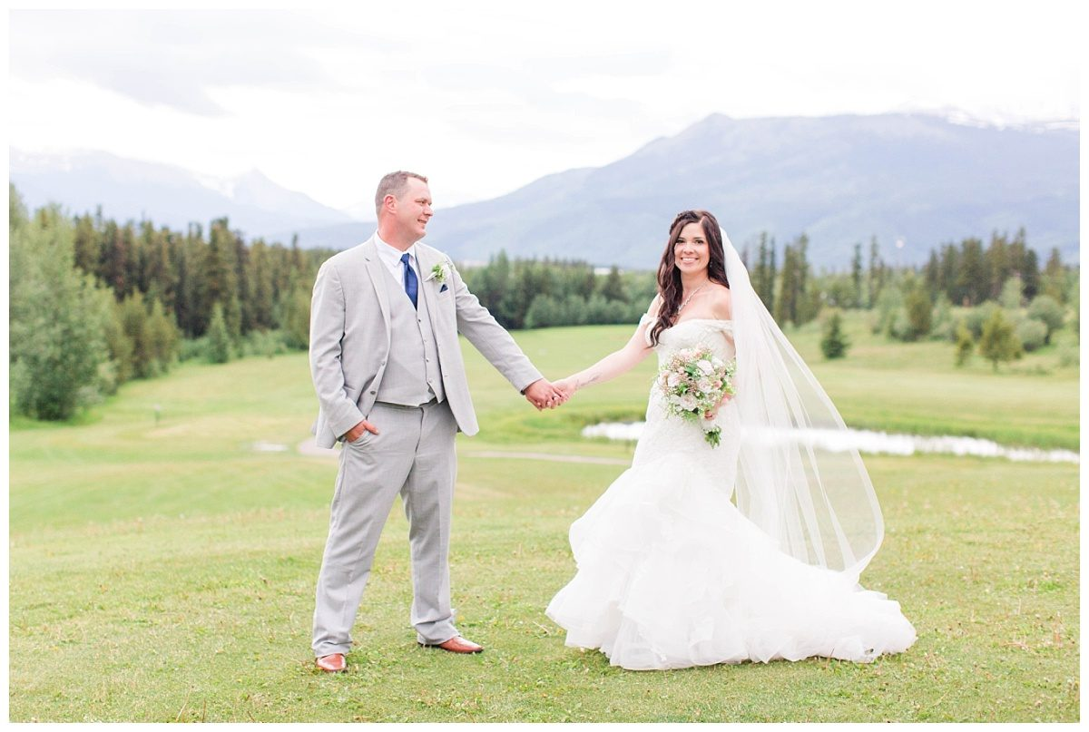 amanda and corwin for their bride and groom portraits at grande cache golf and country club with mountains in the background