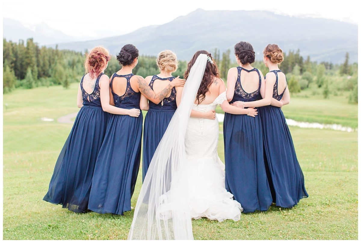 bridemaids looking at the mountains grande cache wedding venue golf country club close up wearing deep blue dress bride wearing her veil blowing in the wind