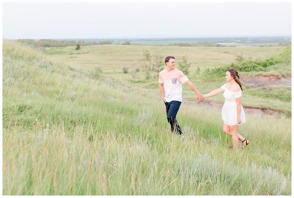 adventurous couple holding hands at kleskun hills in grande prairie alberta very fun