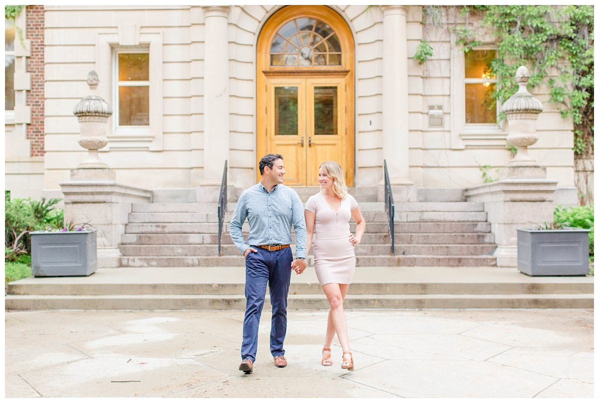 jessie and scott walking in front of the university of alberta for their engagement photos in canada wearing blush pink and navy with brown heels