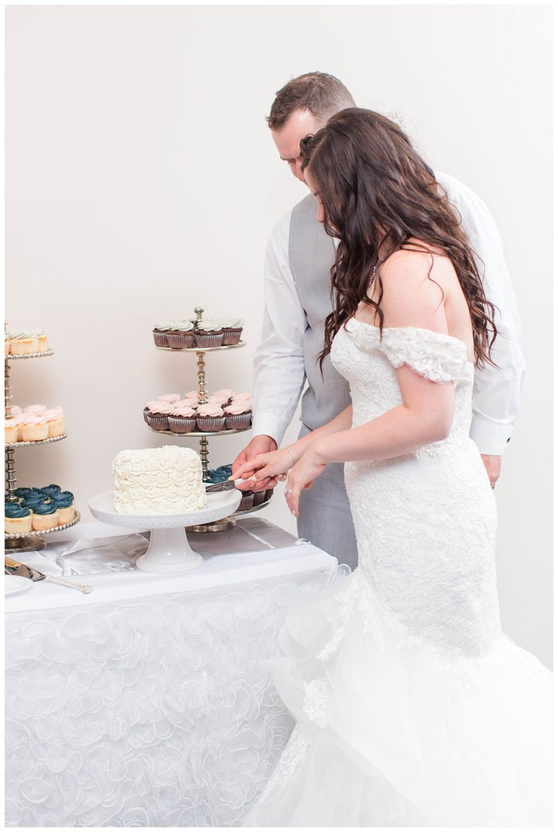 bride and groom cake cutting lots of white light and airy reception style
