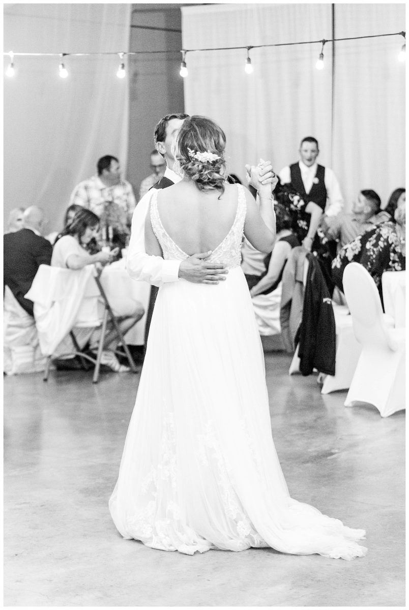 first dance at the recreation center for wedding of mikey and anna in grande cache black and white photo