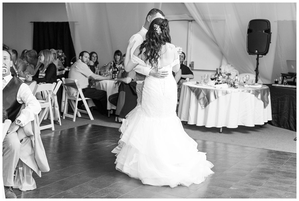 bride and groom dancing during their first dance with their wedding photographer in Alberta