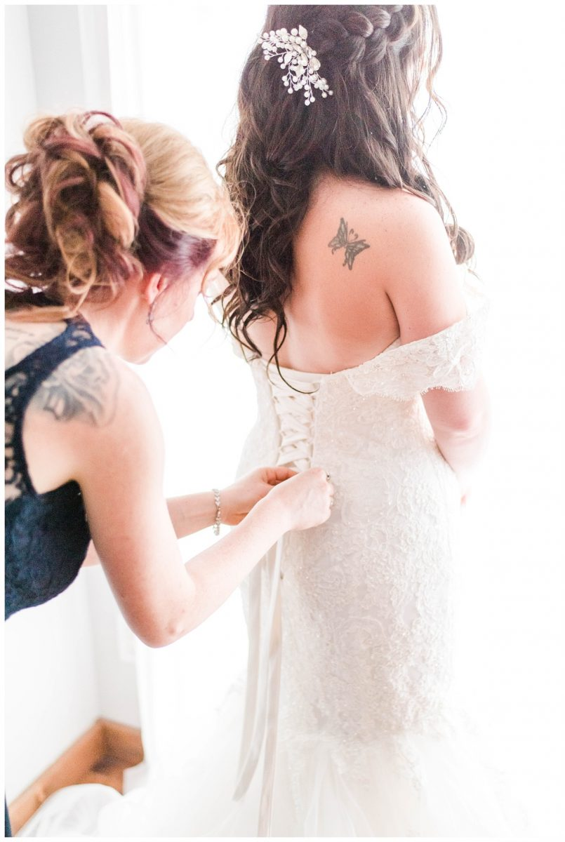bride getting ready putting and tying the wedding dress close up phtoo with bridemaid maid of honor