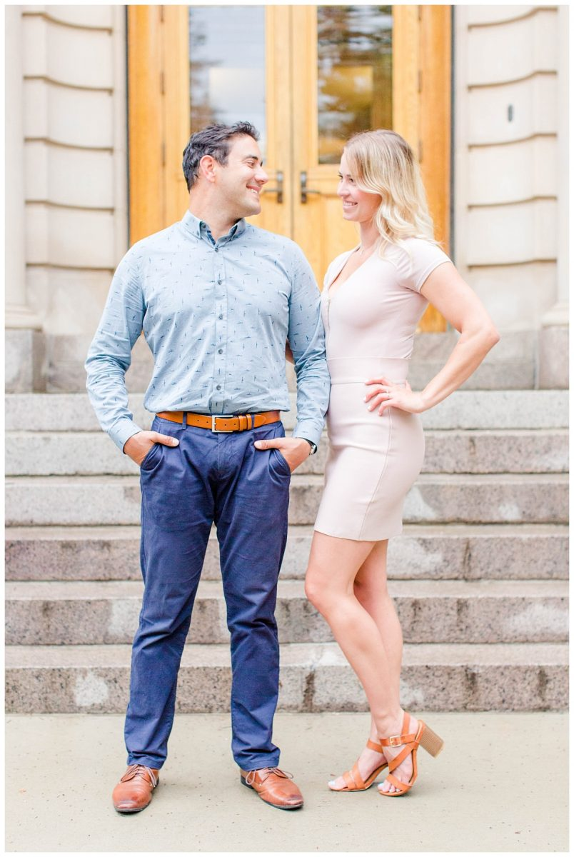 scott and jessie standing up on front historic building in edmonton for their engagement photos with lots of brick and stairs in the background in alberta wearing short blush dress and navy suit and pants brown shoes
