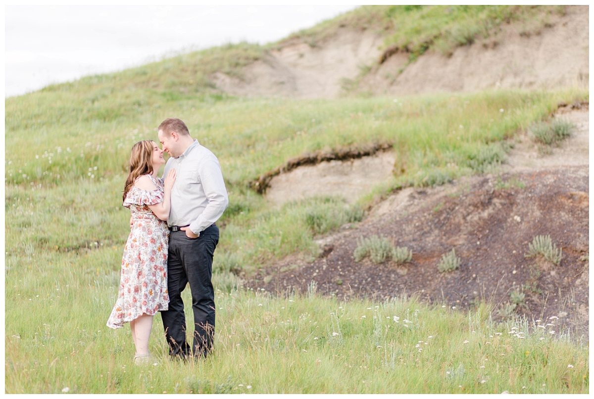 grande prairie engagement photo romantic couple at klesukn hills in Alberta badlands wearing floral dress chest to chest landscape engagement photo