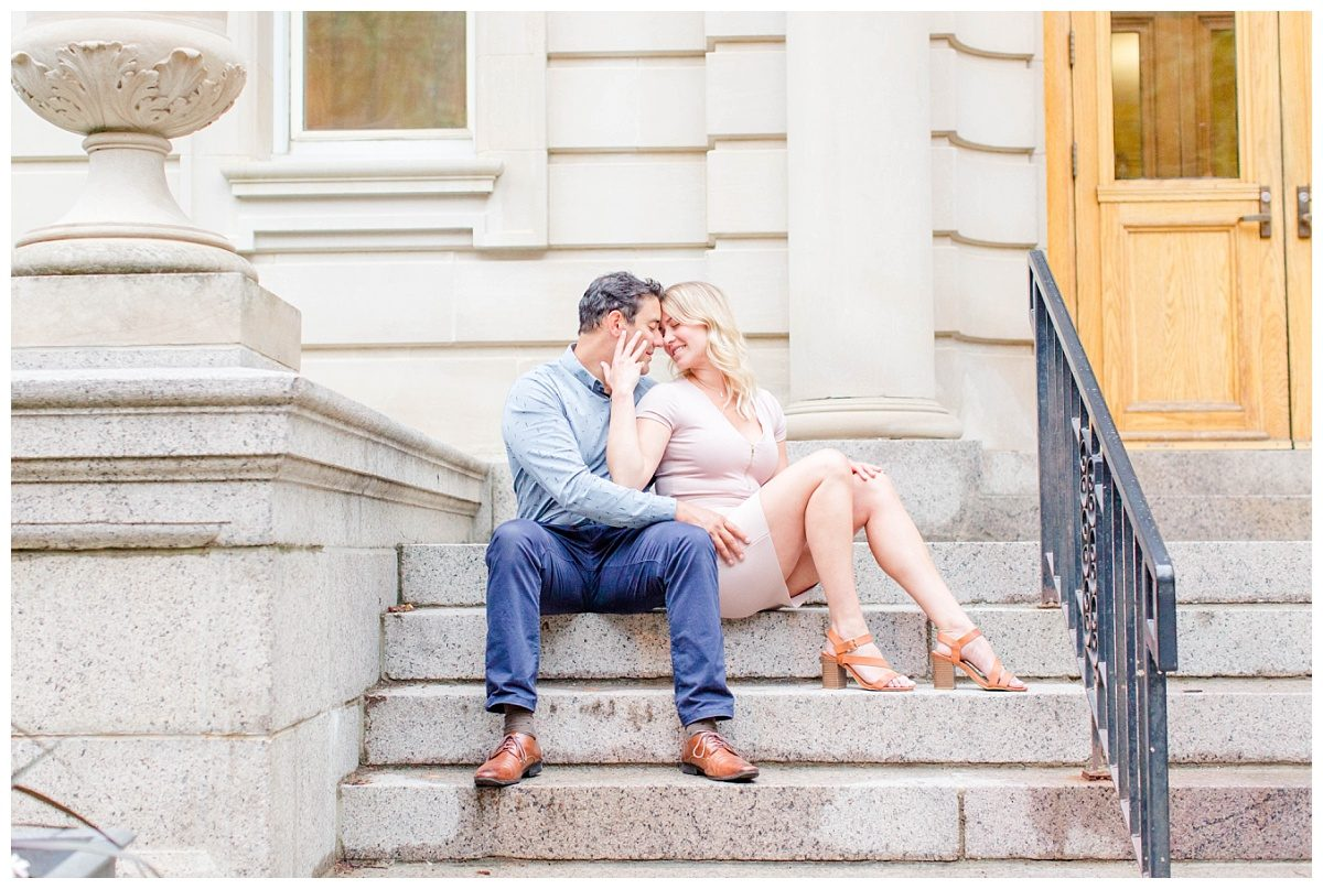 couple sitting down in front of light historic building in edmonton for engagement photos on the stairs
