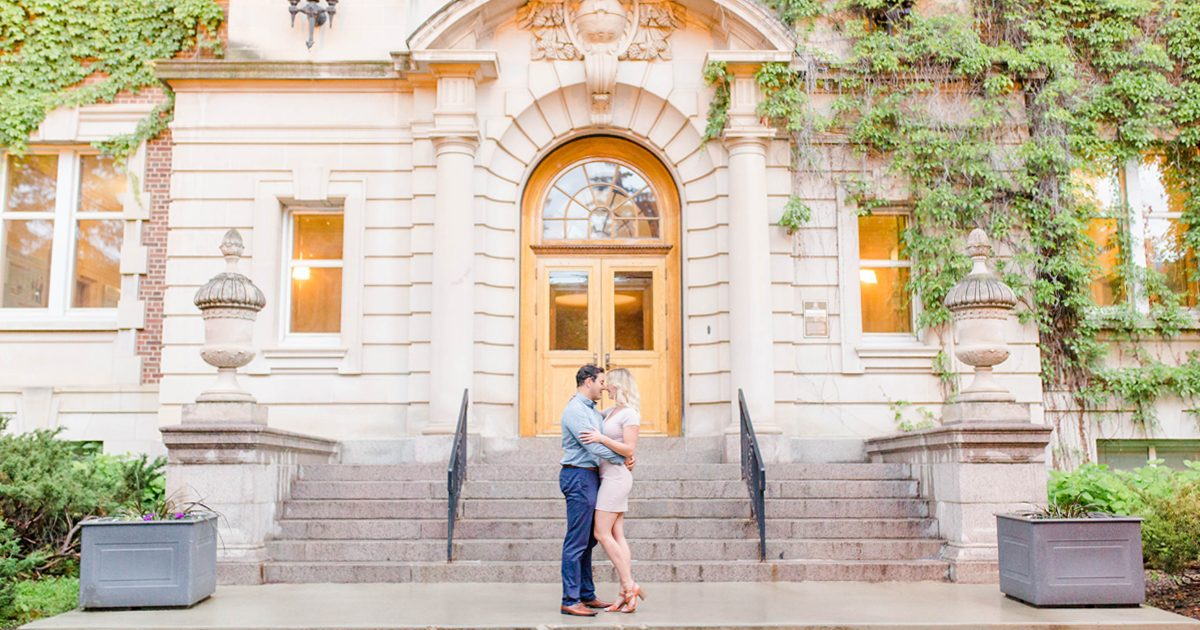 couple engagement photos in front of the university of alberta photographer with historic buildings with vines hanging across then walls with grande prairie wedding photographer