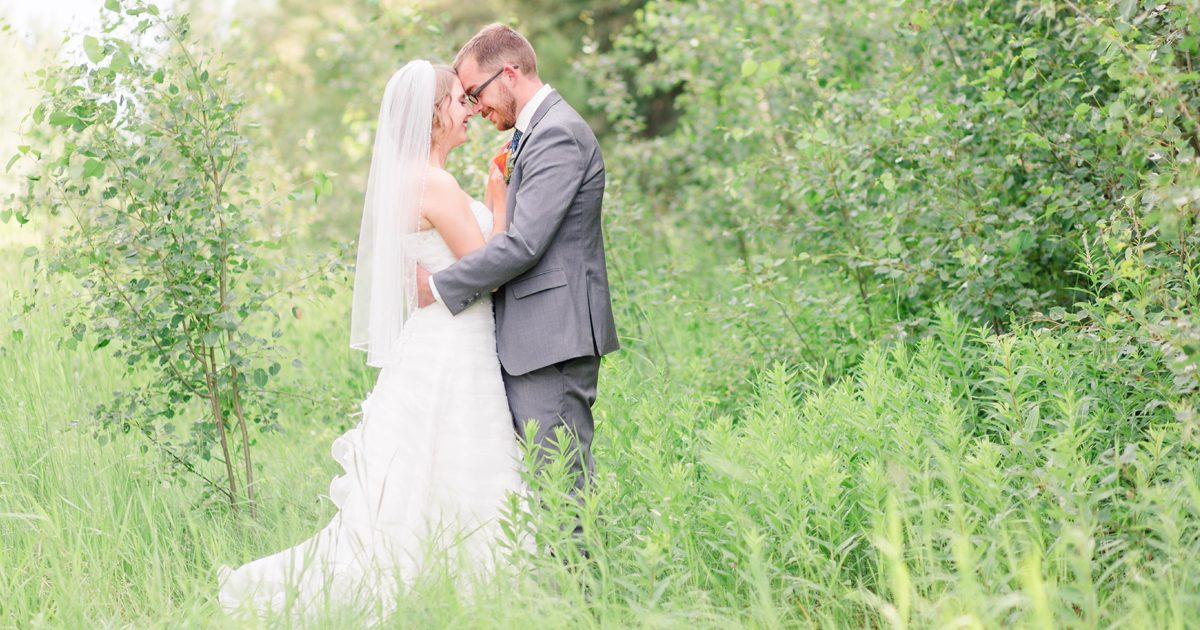 grande prairie spirit river wedding couple for their wedding photography outside at moonshine lake with lots of grass and greens couple romantic elegant nose to nose