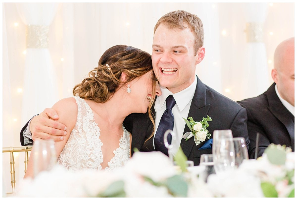 bride and groom laughing during toasts candid moments at the pomeroy hotel in grande prairie