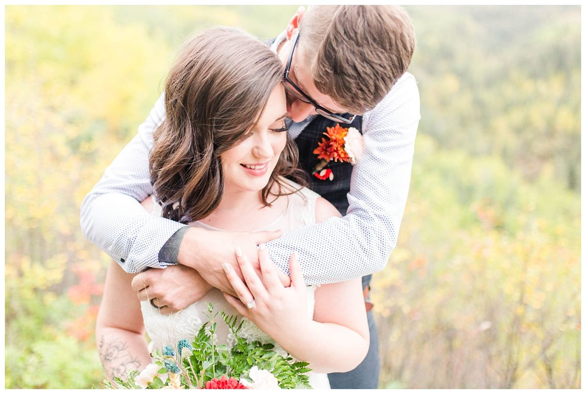 bride and groom nuzzle pose in the fall at serenity acres close up in grande prairie alberta for elopement