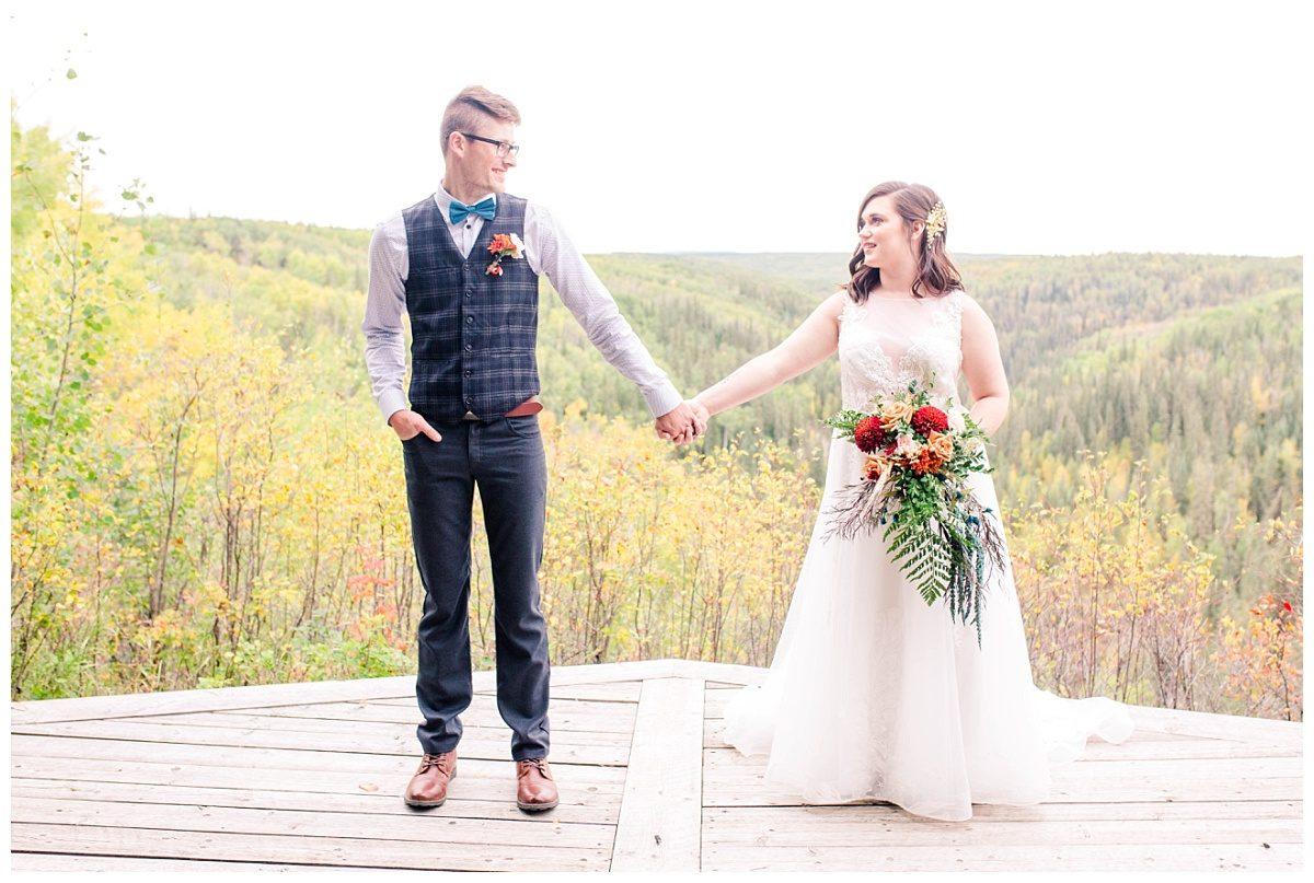 bride and groom holding hands at serenity acres grande prairie alberta with river valley lookout at serenity acres