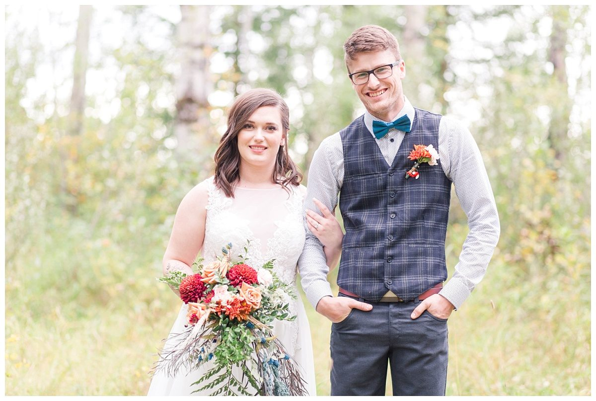 brieanna and jesse smiling and looking at camera at serenity acres in grande prairie fro their bride and groom portraits