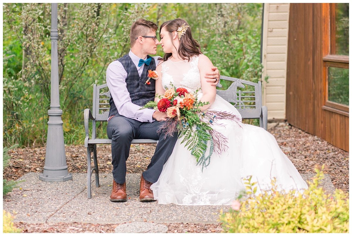 bride and groom nose to nose sitting on the beanch in the fall for elopement at serenity acres