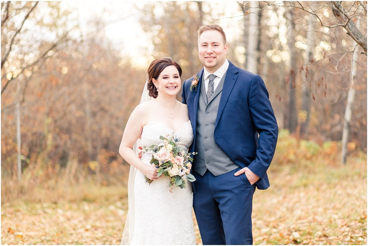 bride and groom smiling for fall wedding photos in grande prairie at muskoseepi park