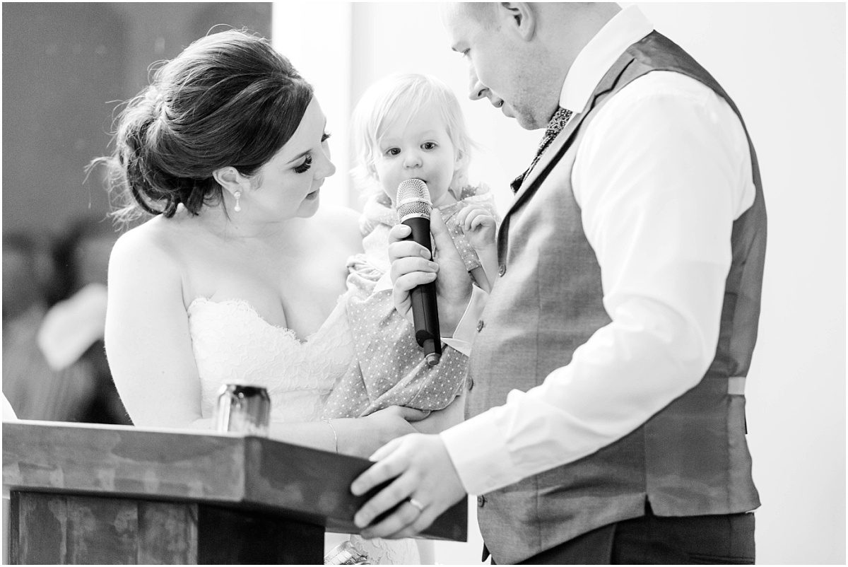 bride and groom with daughter speaking in microphone during speeches nora