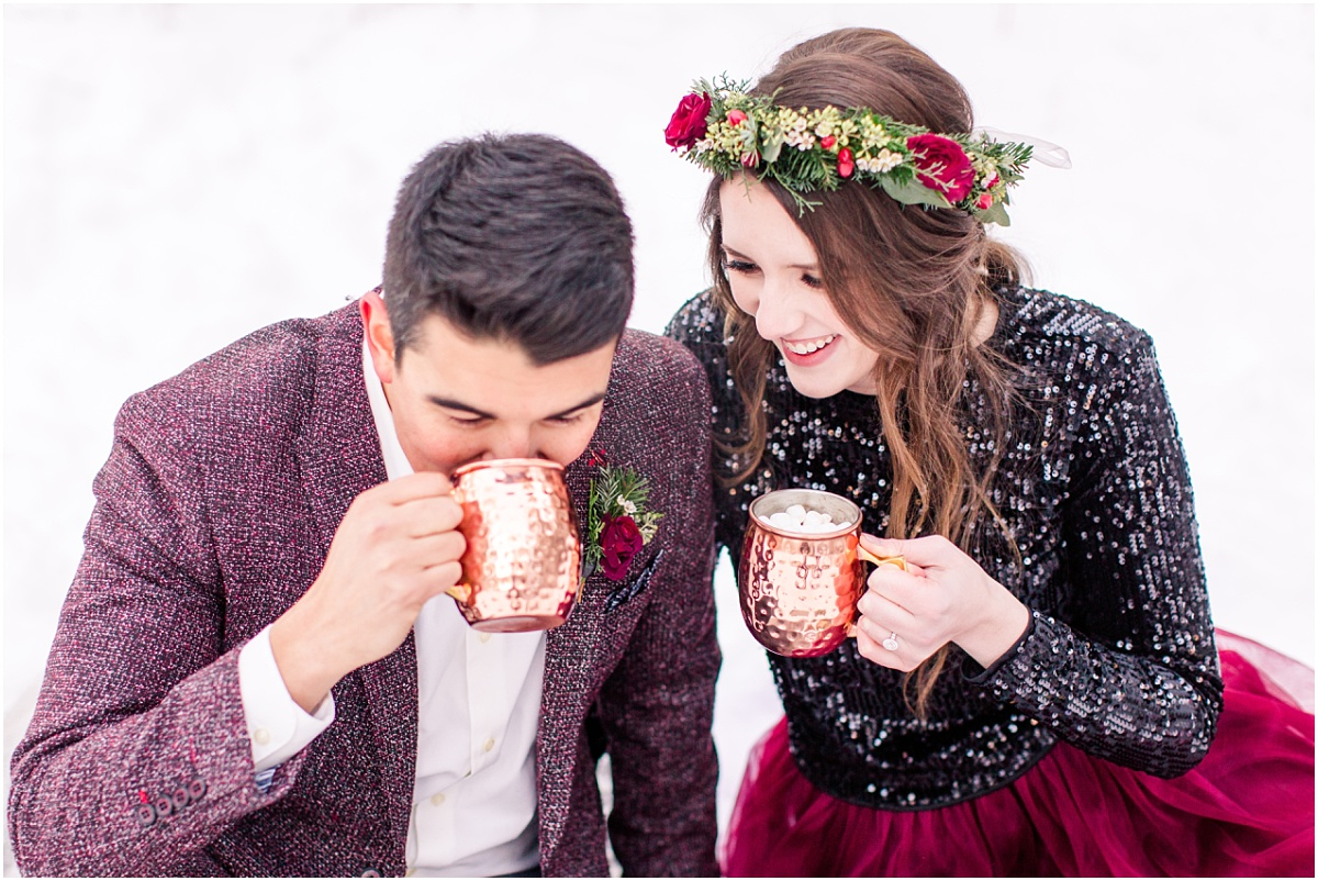 couple drinking hot cocoa winter engagement session with red dress fancy in grande prairie