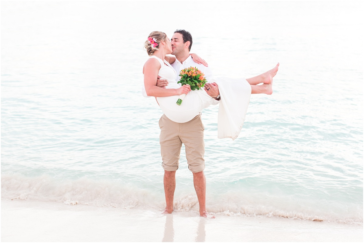 destination wedding photographer in mexico cancun with photographer in the ocean pick up bride