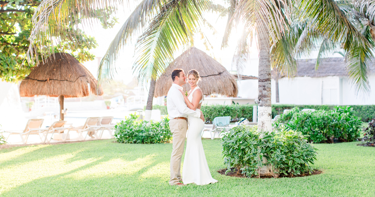 beautiful wedding couple next to the palm trees in mexico cancun for their destination wedding photographer