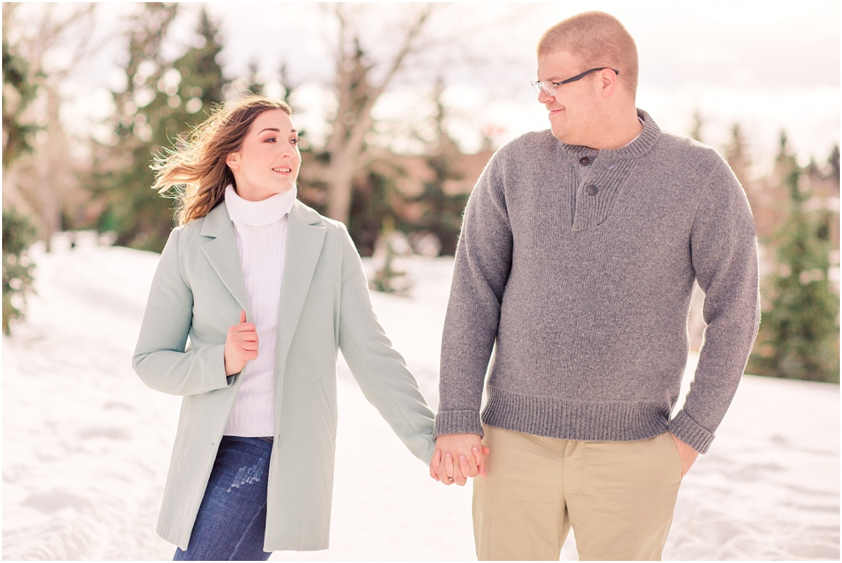 windy engagement session couple holding hands in edmonton in the winter blue and light grey clothing smiling