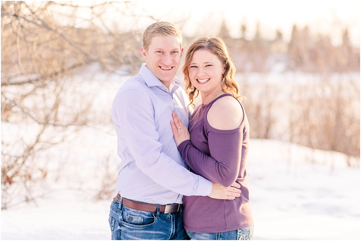 grande prairie engagement with john and alisabeth in the winter spring smiling photo at the camera with background full of glow
