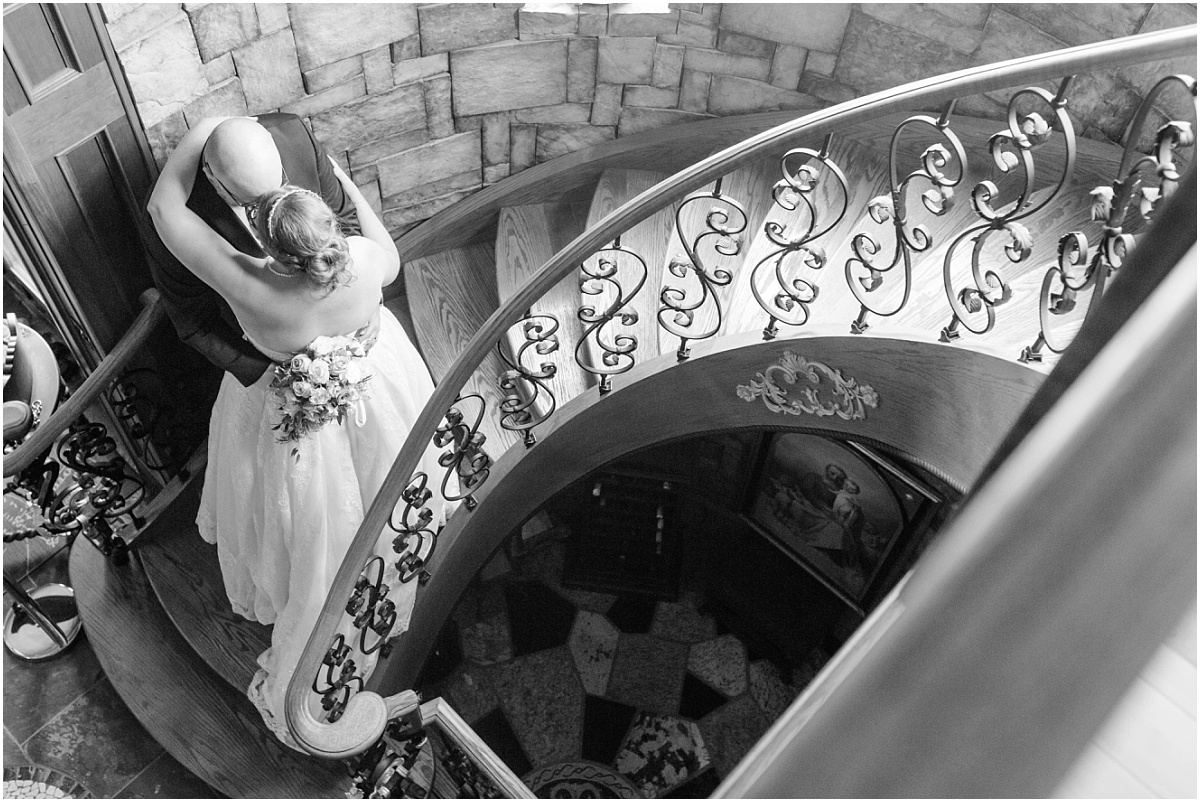 ryans castle photo of bride and groom on the wedding day on the stairs at ryans castle bnb edmonton with photographer black and white