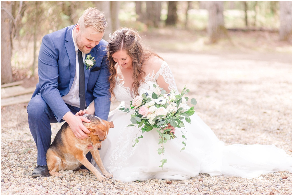 bride and groom petting dog on wedding day in grande prairie alberta with light airy photographer