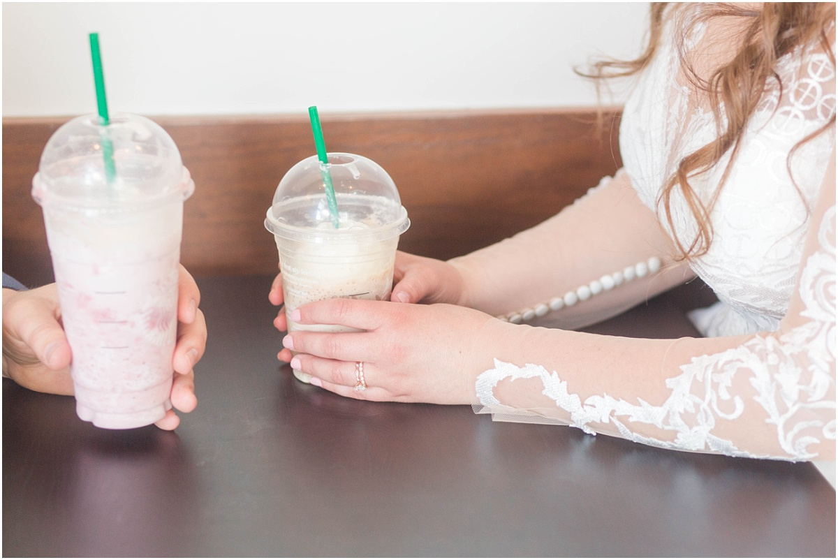 bride and groom sharing coffee at starbucks on their wedding day with wedding ring close up photo