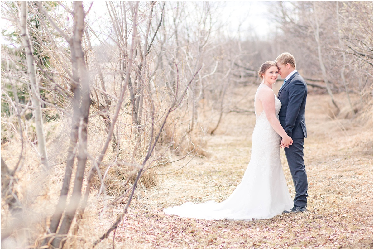 spring covid 19 wedding photos with kayla lynn photographer in grande prairie alberta with light and airy background wide angle shot with tree line.