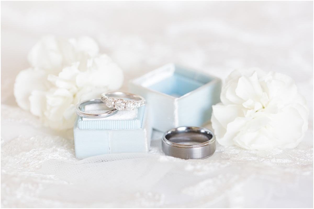 bridal detail photos with blue mrs box with wedding rings and flowers that are white
